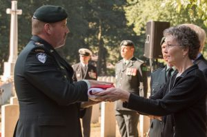 Lieutenant Colonel Ken McClure, Commanding Officer of The Algonquin Regiment, hands the Canadian Flag to Judith Thomas, a second cousin of