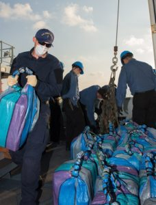 Canadian sailors and members from the United States Coast Guard Law Enforcement Detachment sort packages recovered after being tossed overboard from a vessel of interest during Operation Caribbe on March 25, 2016. Photo: OP Caribbe, DND