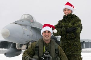 Captain Frédéric Létourneau (kneeling) from 425 Tactical Fighter Squadron at 3 Wing Bagotville, Quebec, is one of the pilots who will escort Santa over North America in 2016. Corporal Steeven Cantin is his crew chief. PHOTO: Corporal Jean-Roch Chabot,