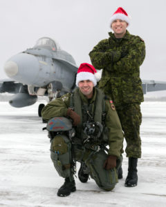 Captain Sébastien Tremblay-Verreault (kneeling) from 425 Tactical Fighter Squadron at 3 Wing Bagotville, Quebec, is one of the pilots who will escort Santa over North America in 2016. Master Corporal Scott Rose is his crew chief. PHOTO: Corporal Jean Roch Chabot,