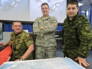 """In anticipation of Santa's travels on Christmas Eve, members of 21 Aerospace Control & Warning Squadron's Delta Flight, from 22 Wing North Bay, Ontario, review Santa's possible course into Canadian air space using a NORAD radar coverage chart. This year's """"Santa Trackers"""" include Captain Jim Mersereau, mission crew commander (left), Lieutenant-Colonel (USAF) Michael Harmon, commander of Detachment 2, First Air Force (centre), and Master Corporal Christian Turcotte, identification supervisor.. PHOTO: Master Corporal Allan Silk"""